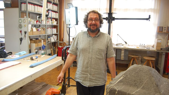 Restaurator Michael Fischer in seinem Atelier mit Werkzeug und vielen Utensilien auf Gestellen. Vorne ein Schwurstein, den er restaurieren muss.