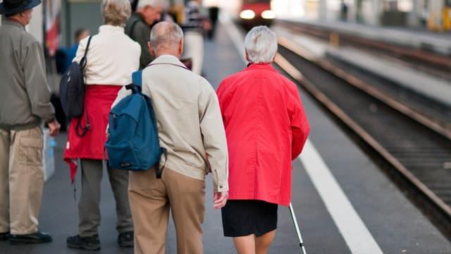 Ältere Menschen gehen ein Perron am Hauptbahnhof entlang