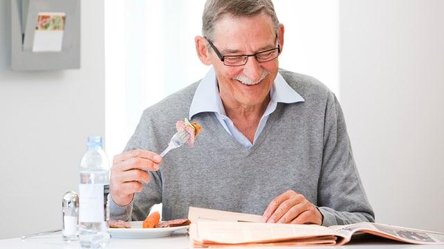 Ein älterer Mann liest Zeitung und lächelt, In der rechten Hand hält er eine Gabel mit Essen.