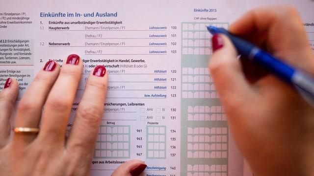 Zwei Hände und ein Stift über Steuerunterlagen.
