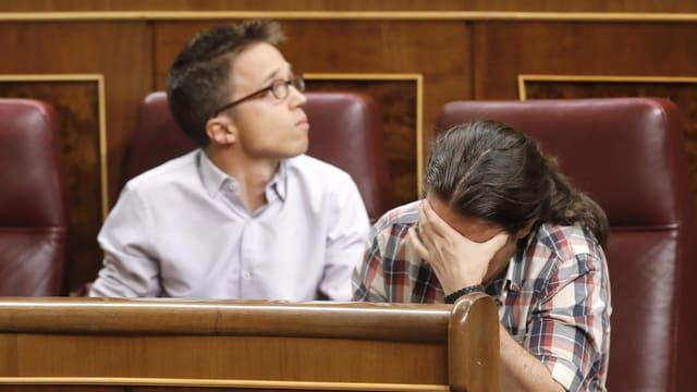 Pablo Iglesias hät sich im Parlament sitzend die Hand vors Gesicht. Sein Sprecher Inigo Errejon sitzt daneben.