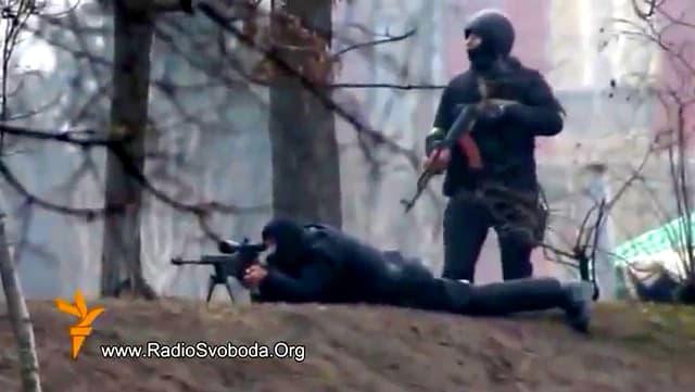 Video-Still mit ukrainischen Soldaten, die mit einem Schweizer Gewehr feuern.