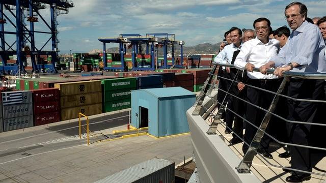 Männer in Anzug auf einem Balkon vor Industriegelände.