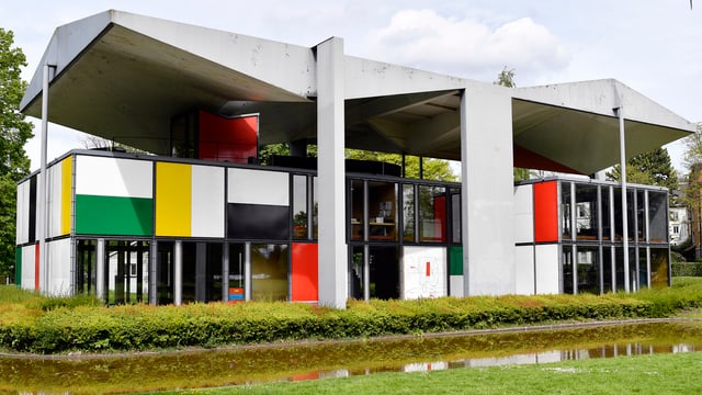 Ein Haus mit Betondach und grossen Glasfronten durchsetzt mit roten, gelben und weissen Platten.