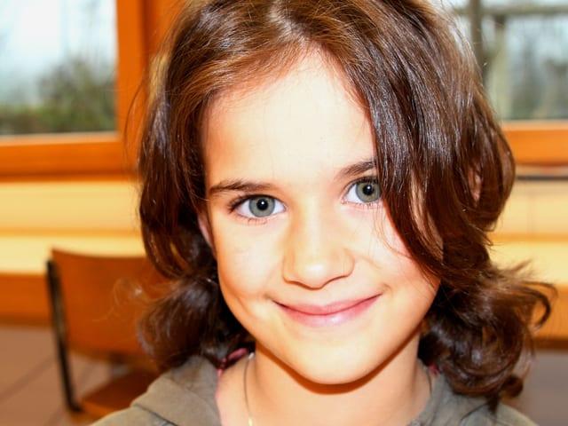 Aurelia, braune Haare, blaue Augen, im Klassenzimmer.