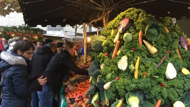 Marktbesucher an Gemüsestand