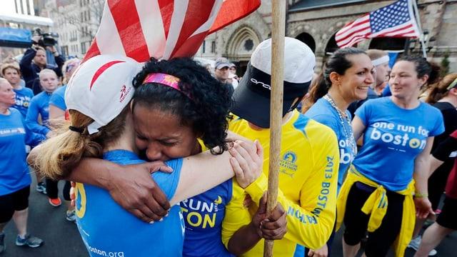 Familienangehörige und Freunde der Opfer gedenken dem Tag. Die Menschen umarmen sich.