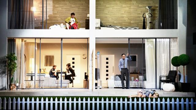 Eine Bühne zeigt ein Haus mit vier Fenstern. Überall sind Schauspieler in den Fenstern.