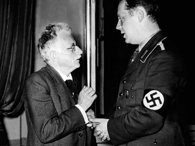 Ein Mann mit Schnauz unterhält sich mit einem Mann mit Swastika an der Uniform.