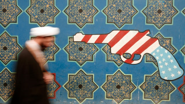 Iranischer Geistlicher läuft an einem Graffiti an der ehemaligen US-Botschaft in Teheran vorbei.