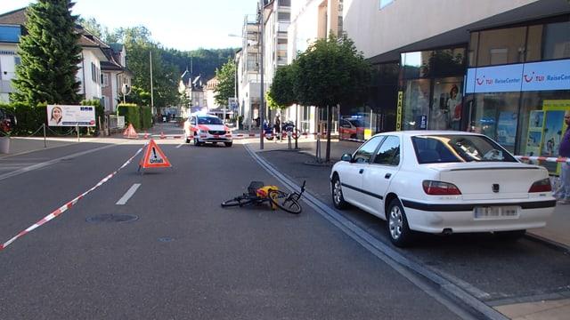 Polizeifoto des Unfallorts mit dem umgestürtzten Velo auf der Strasse.