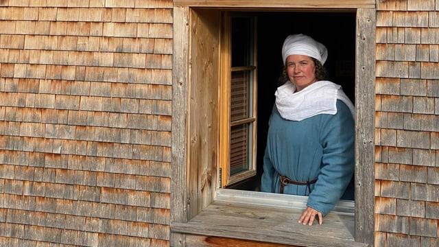 Ein Frau mittleren Alters, gekleidet wie im Hochmittelalter, schaut aus einem Holzhaus.