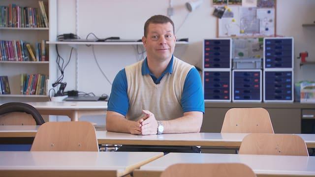 Ein Mann mittleren Alters sitzt an einem Tisch in einem Schulzimmer. Hinter ihm steht ein Bücherregal und mehrere Utensilien für den Schulgebrauch.