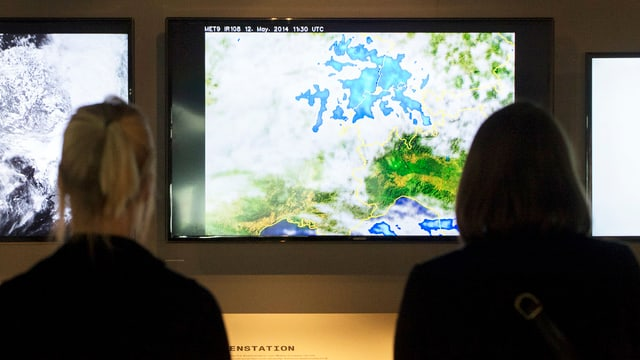 Zwei Frauen schauen Meteo-Bildschirm an.