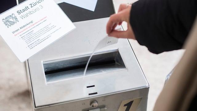 Eine Wahlurne im Kreis 3 in der Stadt Zürich. Eine Person wirft gerade seinen Zetteln ein.