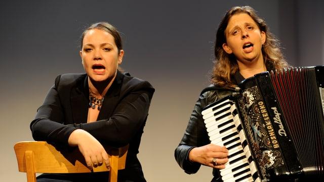 Die beiden Kabarettistinnen Nicole Knuth, singend und Olga Tucek, Akkordeon spielend und singend.