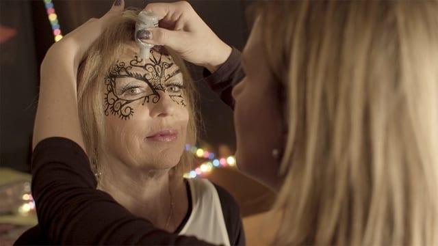 Frau wird geschminkt.