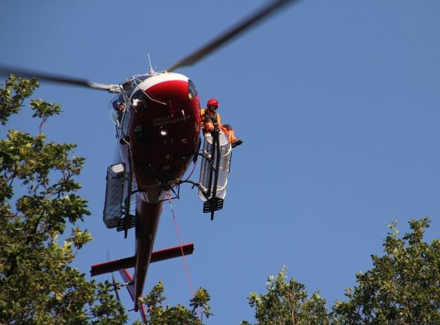 Ein Helikopter fliegt ein paar Meter über den Baumwipfeln.