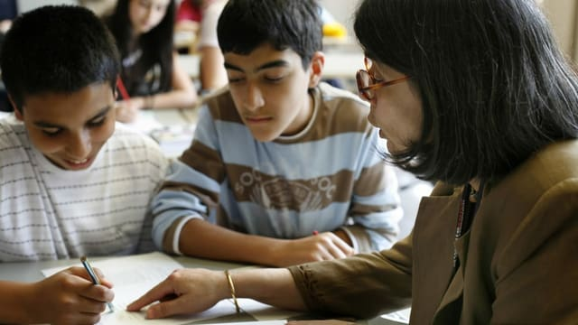 Lehrerin gibt zwei Schülern Nachhilfe