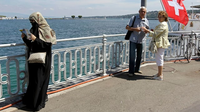 Frau mit Gesichtsschleier und starrendes älteres Schweizer Paar am See
