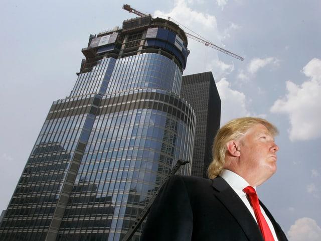 Donald Trump von unten fotografiert vor einem Hochhaus