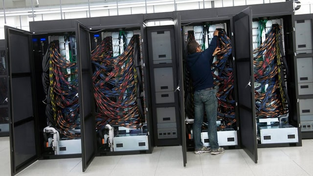Drei offene Schränke voller Kabel, die mehrere Rechner miteinander verbinden.