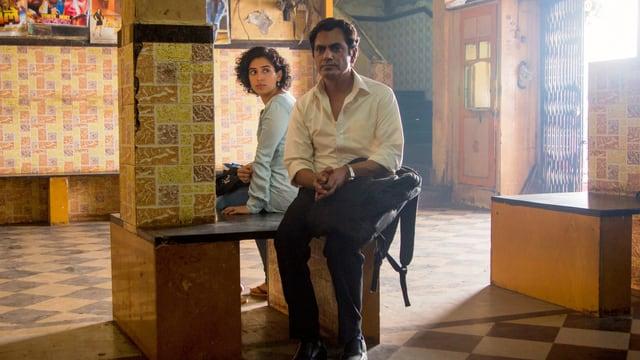 Eine Frau und ein Mann sitzen in einem Raum, der aussieht wie ein Warte- oder Vorzimmer.