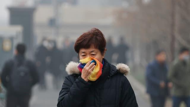 Frau hält Schal vors Gesicht während sie im Smog unterwegs ist
