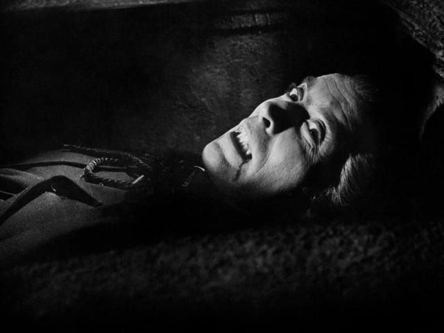 Schwarzweiss-Bild. Lee mit Dracula-Zähnen und aufgerissenen Augen in einem Sarg.