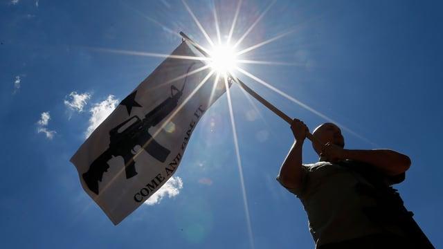 Ein Mann schwenkt eine Fahne mit einem Gewehr.