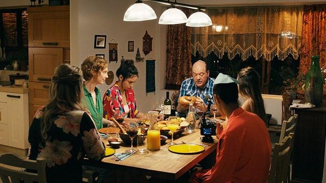 Filmausschnitt: 6 Menschen sitzen um einen Tischen und Essen.