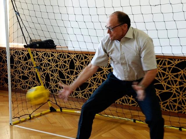 Ein Mann in Hemd steht in einer Turnhalle in einem Fussballtor. Neben ihm saust ein gelber Ball vorbei ins Goal.