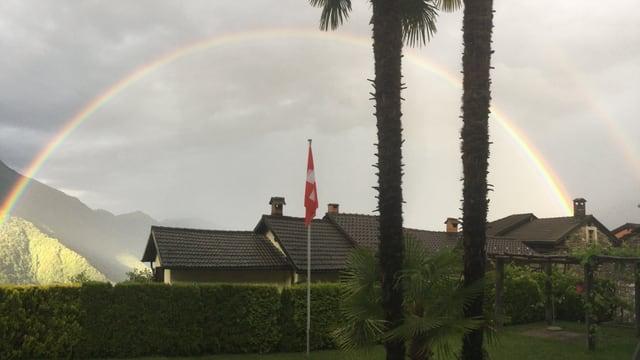Regenbogen hinter Palmen und Tessiner Häusern.