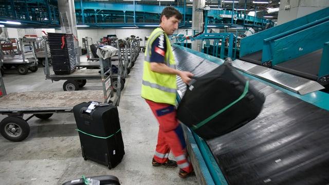 Ein Mitarbeiter von Swissport wuchtet einen Reisekoffer vom Gepäckband.
