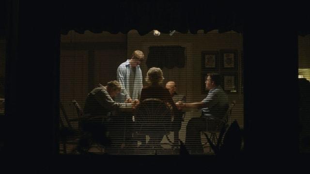 Blick von aussen auf ein Wohnzimmer. Drinnen scheint eine hitzige Diskussion stattzufinden.