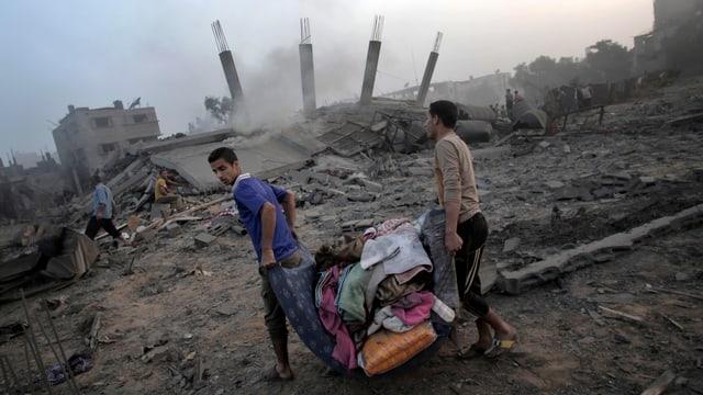 Zwei Palästinenser tragen Habseligkeiten durch ein zerbombtes Gebiet