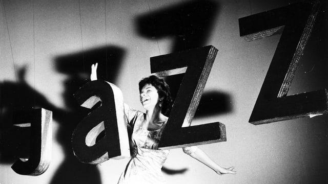 Das Wort Jazz hängt in grossen Buchstaben auf die Bühne. Dahinter steht Inge Brandenburg als junge Frau und hält die Arme zu Flügeln ausgebreitet.