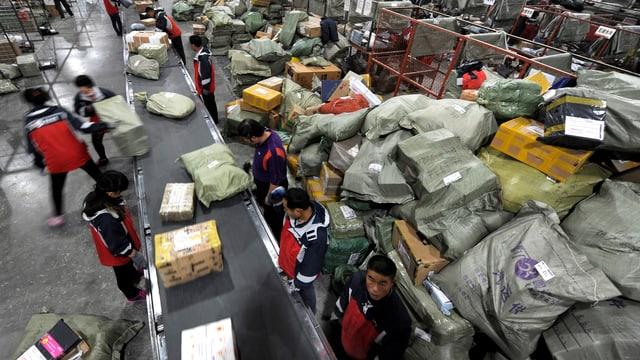 Alibaba-Mitarbeitende sortieren Pakete in einer Speditionshalle.