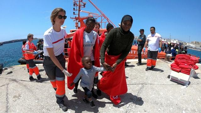 Freiwillige Helfer des Roten Kreuzes leisten den Ankömmlingen Erste Hilfe.