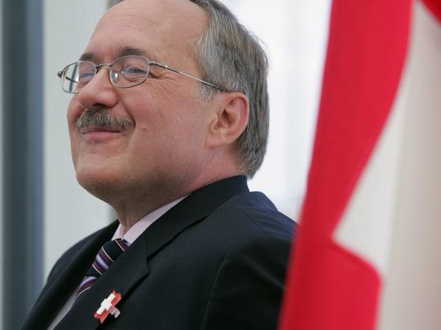 Samuel Schmid neben einer Schweizer Fahne