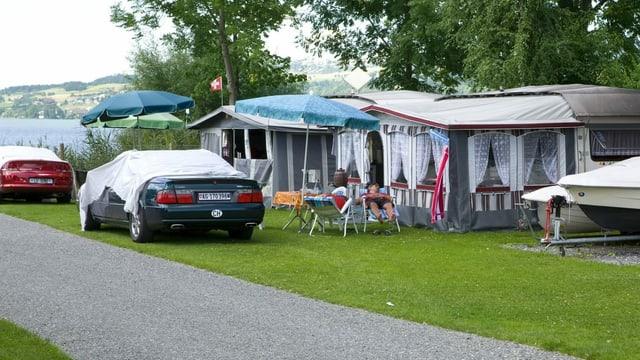 Wohnwagen mit Vorzelten und davor parkierte Autos auf einem Campingplatz.