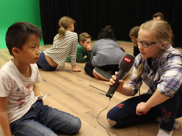 Kind interviewt Kind mit einem SRF Mikrofon