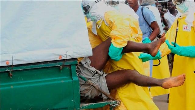 Männer in Schutzanzügen verfrachten einen Ebola-Kranken in eine Ambulanz