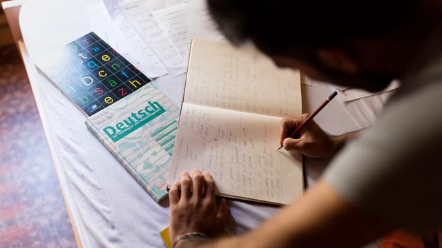 ein Mann schreibt in ein Heft. Auf dem Tisch liegen Deutschbücher