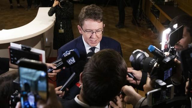 Albert Rösti umringt von Reportern.
