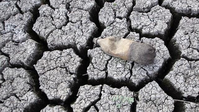 Ein leere PET-Flasche auf einem ausgetrockneten Lehmboden