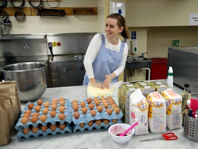 Bäckerin vor vielen Zutaten am Teig kneten.