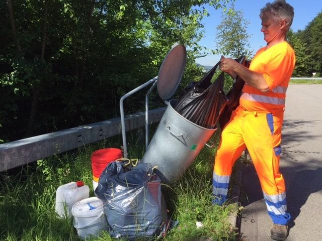 Mann in orangem Anzug vor Abfalleimer.