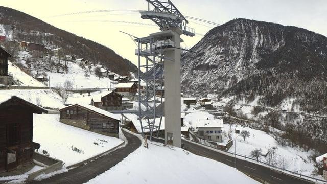 Seilbahn-Zwischenstation, dahinter ein paar Häuser im Schnee