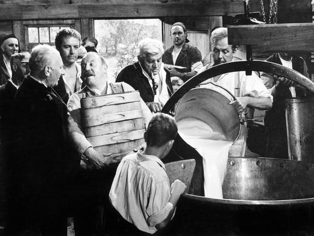 Szene in einer Molkerei. Mehrere Männer liefern Milch. Ein Kessel Milch wird gerade in einen grossen Bottich geschüttet. Ein Junge schaut dabei zu.